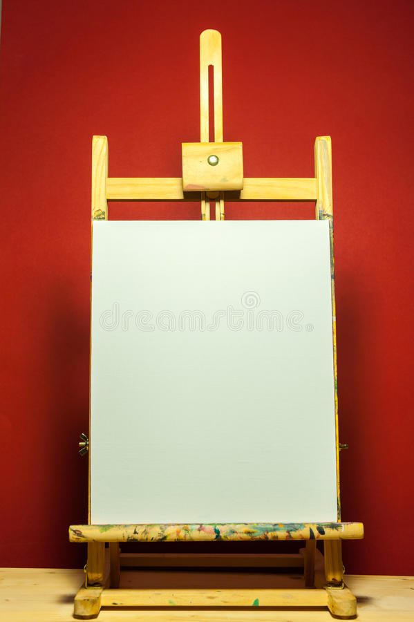 Painting easel with white canvas for text in dramatic light. And red background stock photos