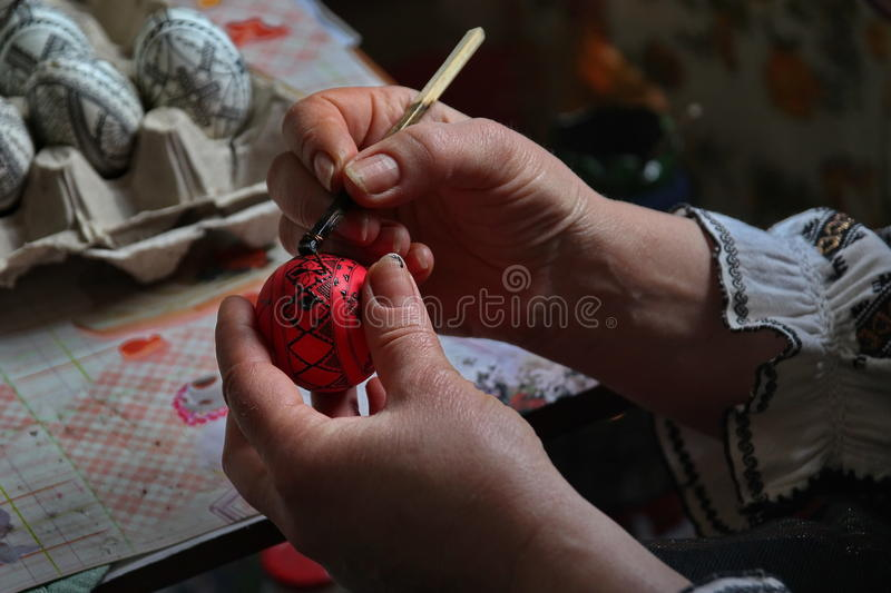Painting the egg. Unidentified romanian woman painting the eggs for the traditional easter. Photo taken on: April 30th, 2014 in Bucovina, Romania stock photography