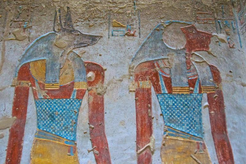 Painting of Egyptian god of Anubis and another god in the Valley of Kings in Luxor, Egypt. Painting of Egyptian god of Anubis and another god in the Valley of stock photography