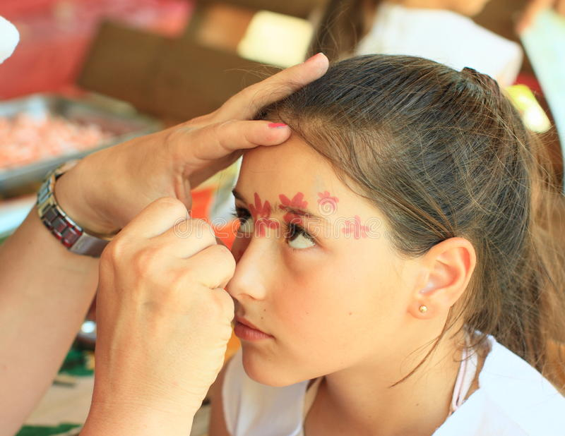 Painting on face. Painting blossomes on face of little kid - brunette girl stock photos