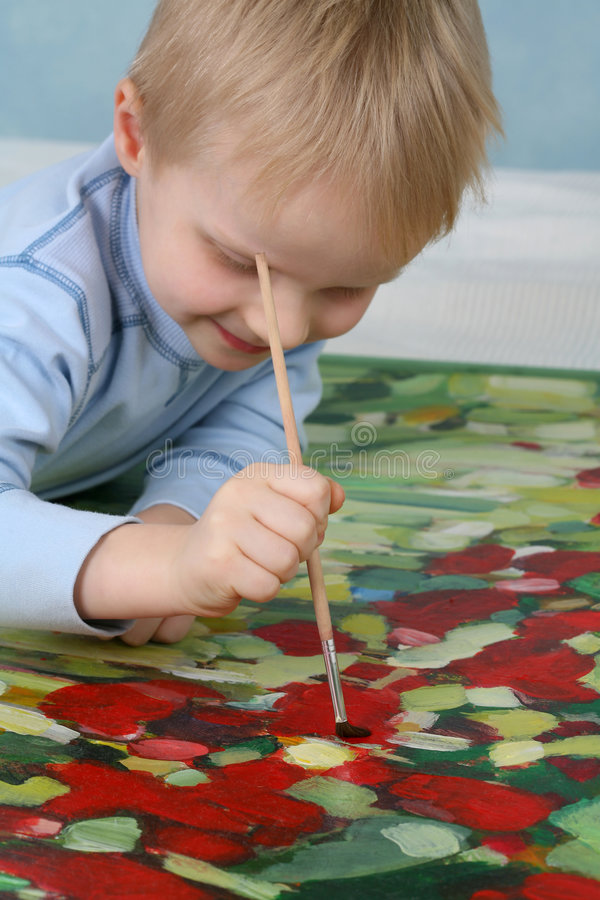 Painting Flowers. A young boy painting colorful flowers royalty free stock images