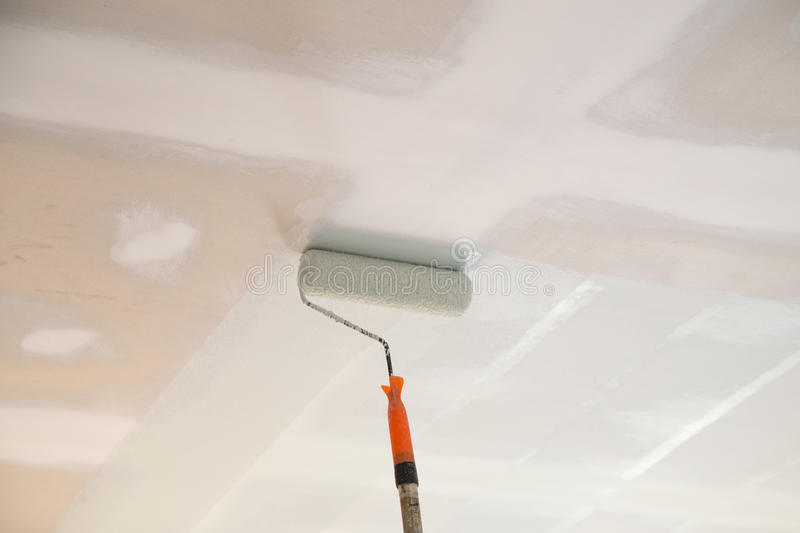 Painting a gypsum plaster ceiling with roller stock images
