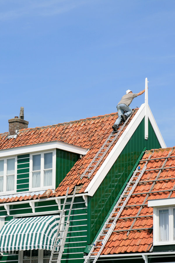 Painting a house. A man on the top of the roof is painting the highest place of a house in Marken, the Netherlands stock photo