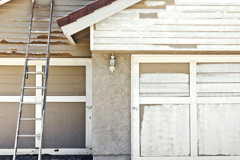Painting a House. Ladder used to help paint the front view of a home royalty free stock photo