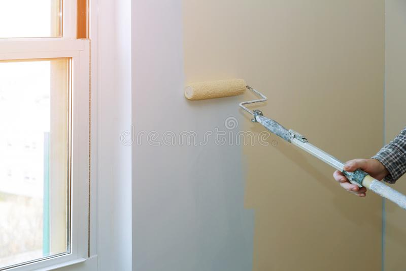 Male hand painting wall with paint roller. Painting apartment, renovating with color paint. Painting male hand walls with paint roller apartment, renovating with stock photos