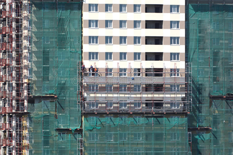 Painting of new high building with workers. Green building grid stock images