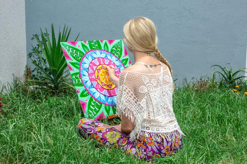 Painting outdoors, a young woman blonde draws a mandala on the nature sitting in the grass vector illustration