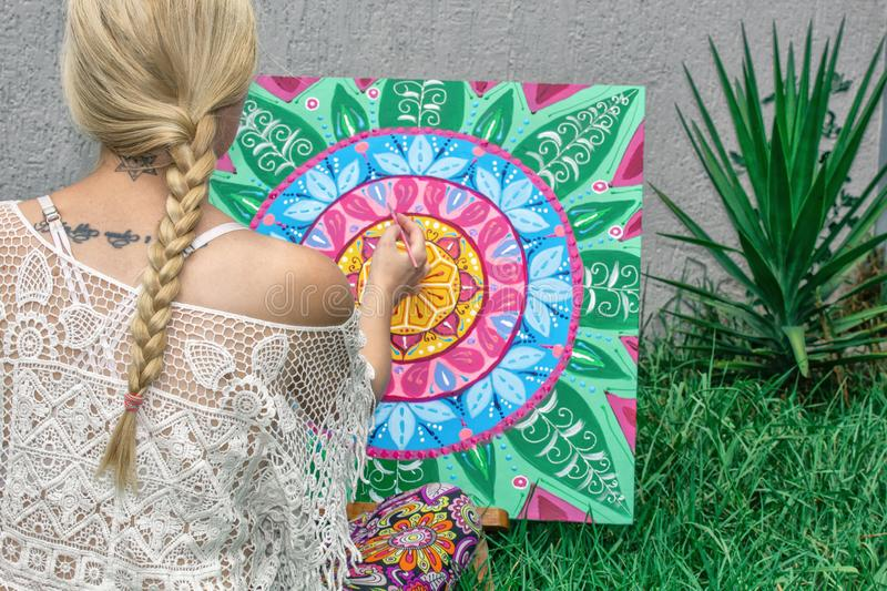 Painting outdoors, a young woman blonde draws a mandala on the nature sitting in the grass royalty free stock images