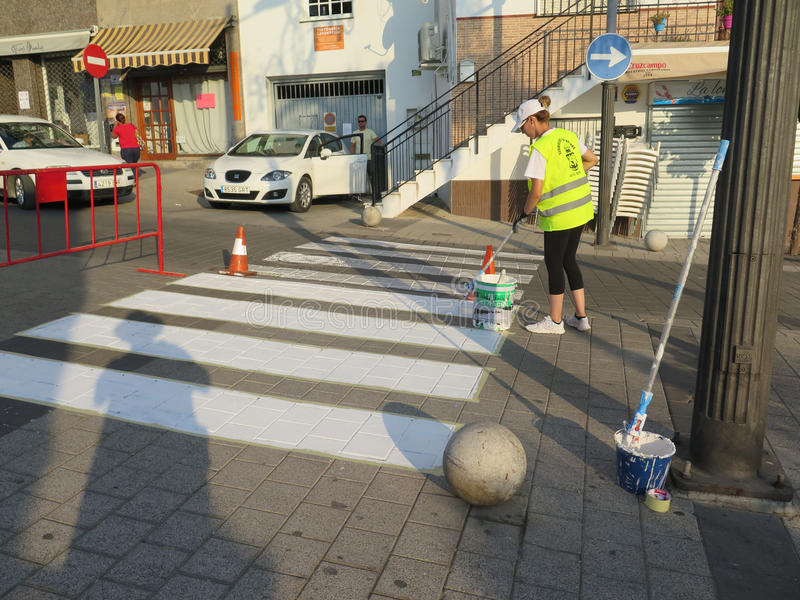 Painting pedestrian crossing markings. Alora, Spain - July 27, 2017: Female worker painting white parts of pedestrian crossing on road in andalusian village royalty free stock images