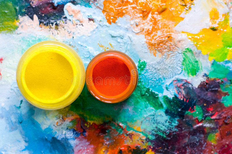 Painting pigment. Painring palette and oil pigment, focus on orange pigment royalty free stock image
