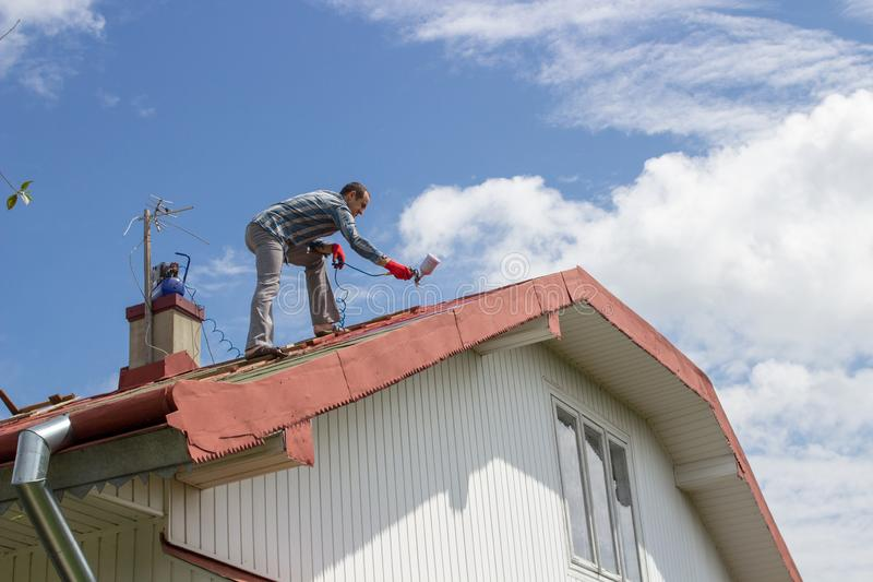 Painting the roof of the house,A man high on the house paints a roof in red with the background of a blue sky stock image