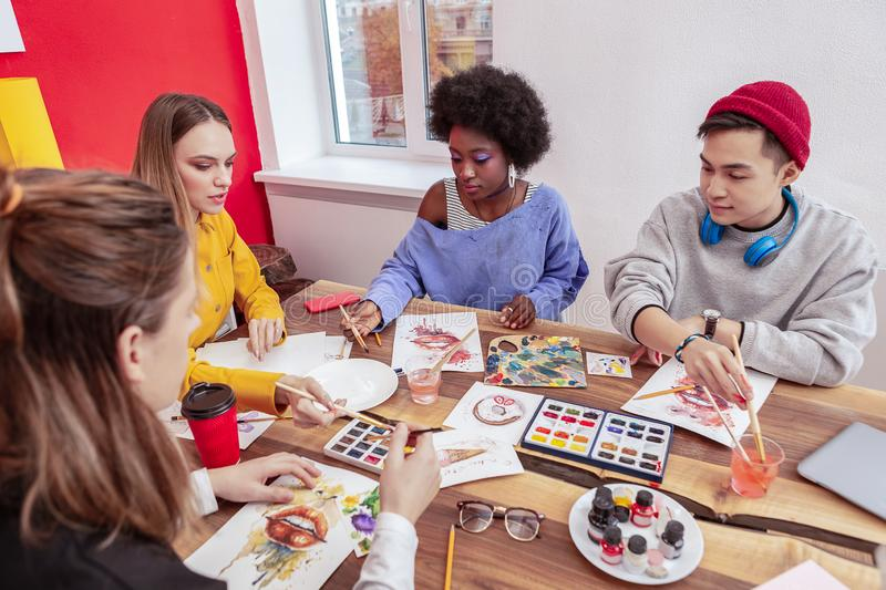 Four art students sitting at the table while painting together. Painting together. Four creative art students sitting at the table while painting together royalty free stock images