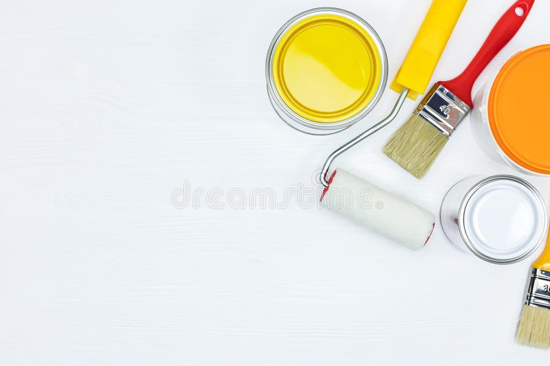 Painting tools for house renovation on white wooden background. Painting tools for house renovation. paint cans, roller and brushes on white wooden background royalty free stock photos
