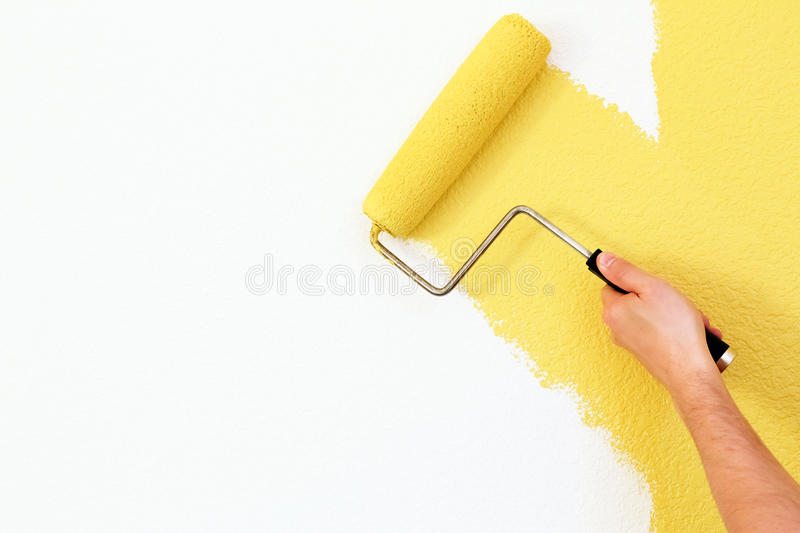 Painting a wall. Painting a house wall with roller royalty free stock photo