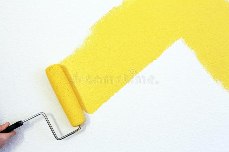 Painting a wall. Painting a house wall with roller stock photography