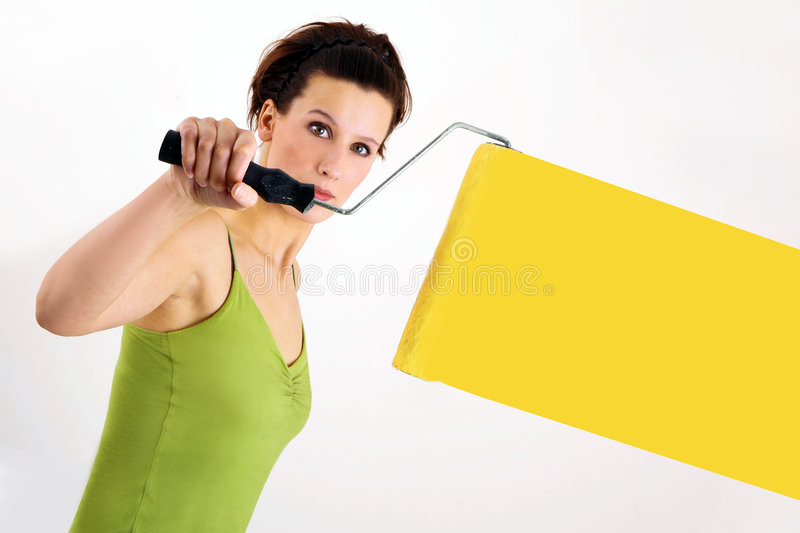 Painting the wall. Woman painting on wall using paint roller stock images