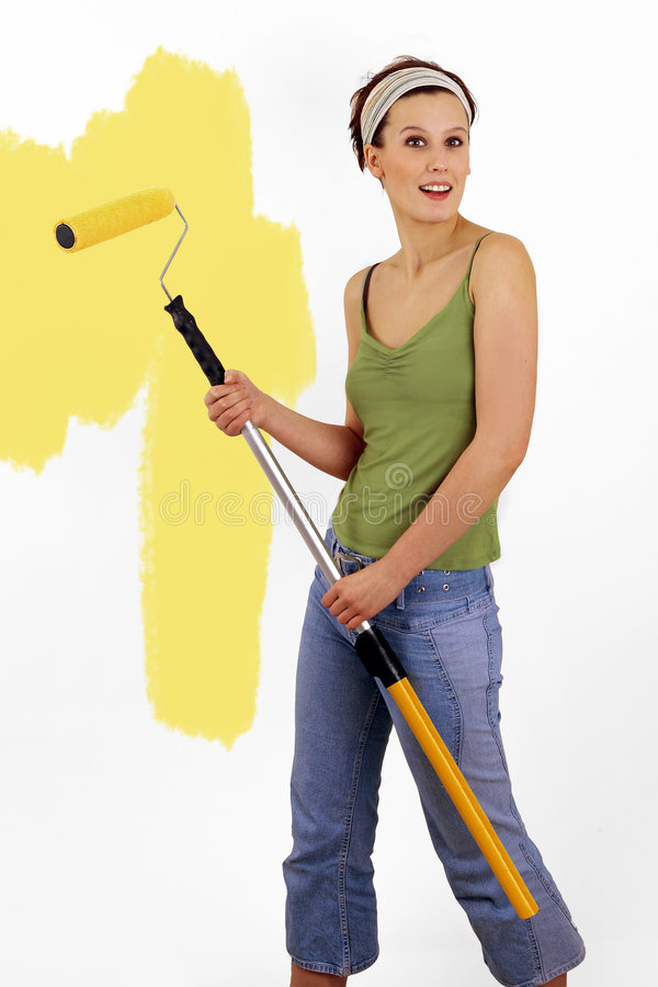 Painting the wall. Woman painting on wall using paint roller royalty free stock photography