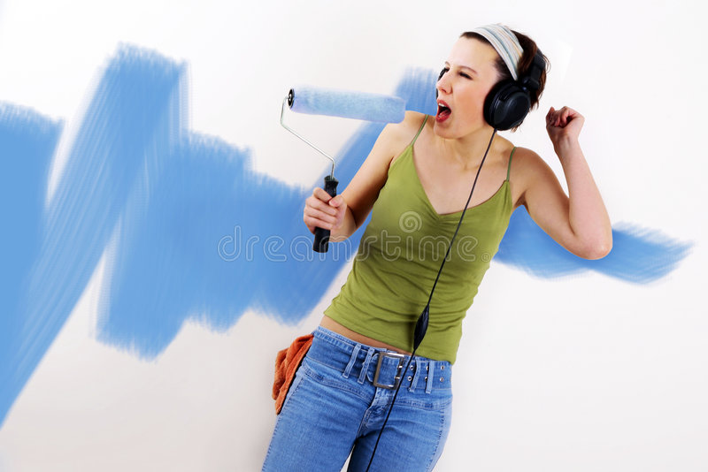 Painting the wall. Woman painting on wall using paint roller royalty free stock image