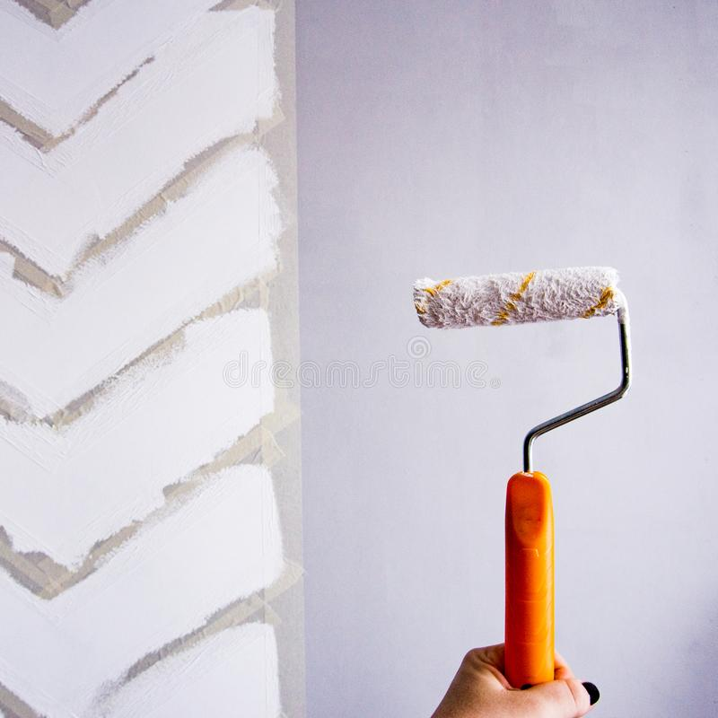 Painting a wall with masking tape. white zigzag strips on grey wall. hand holding the roller with paint royalty free stock photo