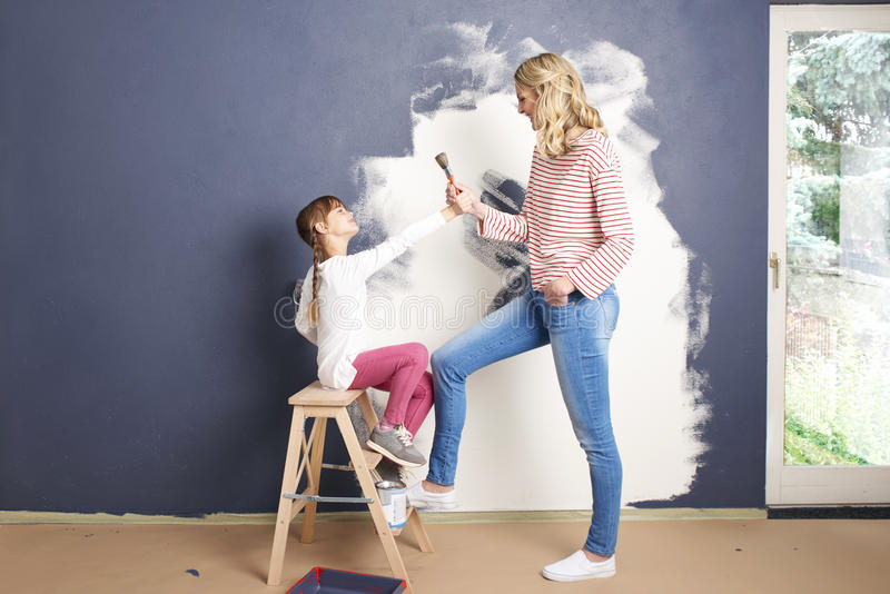 Painting wall. Portrait of a cute daughter and her mother painting wall in their living room royalty free stock photo
