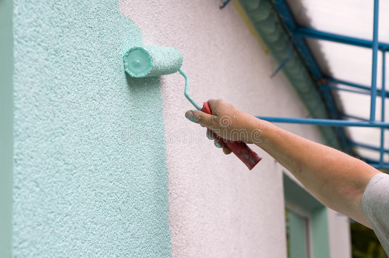 Painting wall with a roll in green royalty free stock image