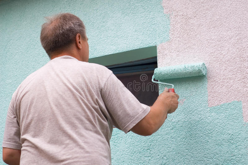 Painting wall with a roll in green royalty free stock photo