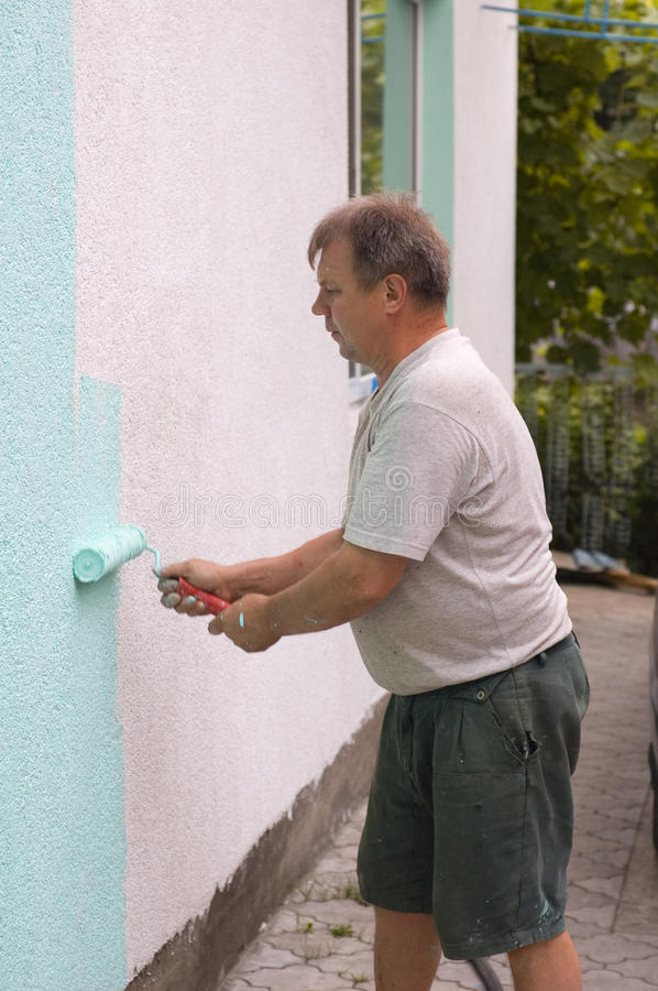 Painting wall with a roll in green stock photo