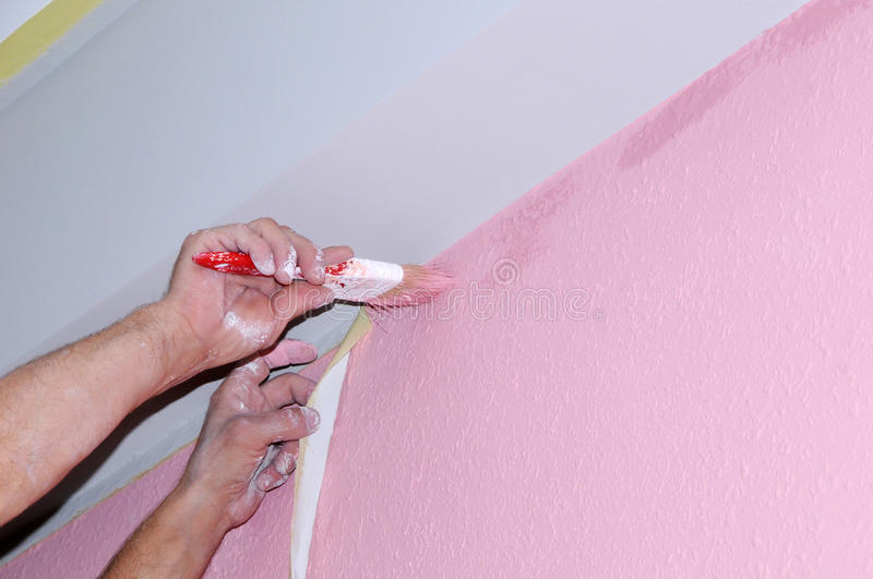 Painting wall of room. painting voids after masking tape. hands in the paint, close-up royalty free stock photography