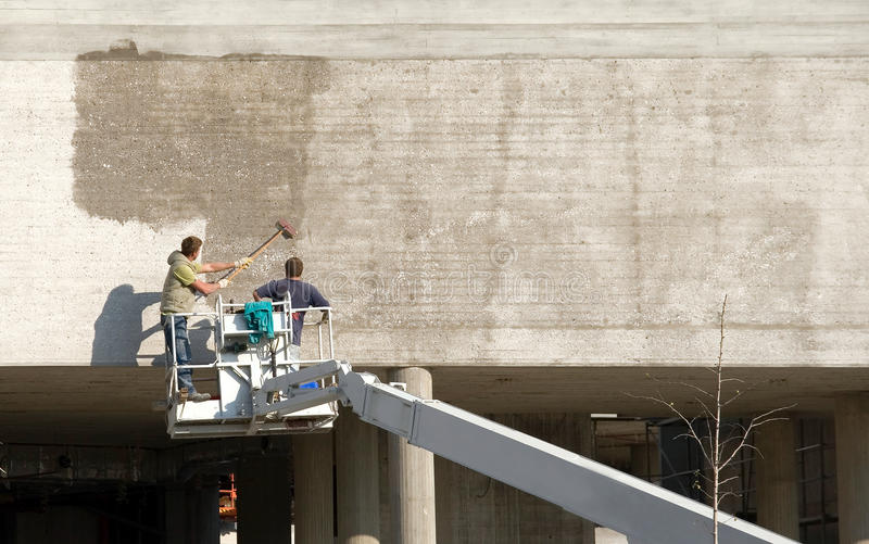 Painting a wall. Workers on lift insulate concrete wall stock photos