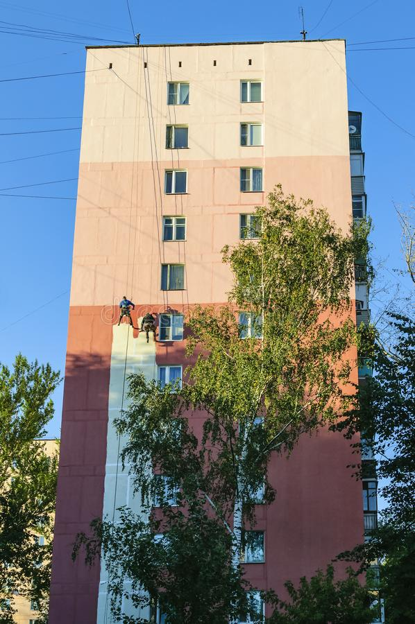 Painting the walls and facade of a multi-storey residential building at high altitude by industrial climbers royalty free stock image