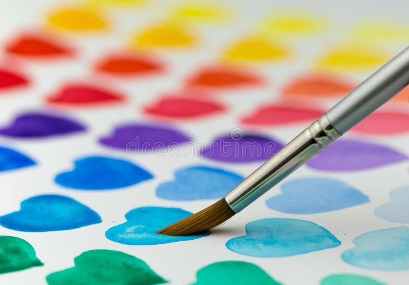 Painting watercolor hearts with a paintbrush. Shallow depth of f. Multicolored hearts being painted with a watercolor paintbrush and paint. Narrow depth of field royalty free stock photos