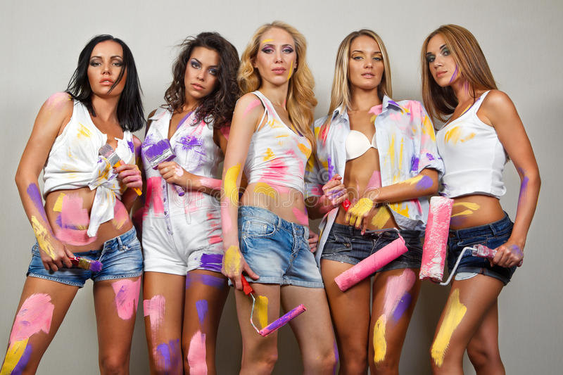 Painting women with brushes. Party of cheerful young painting women with brushes stock photos