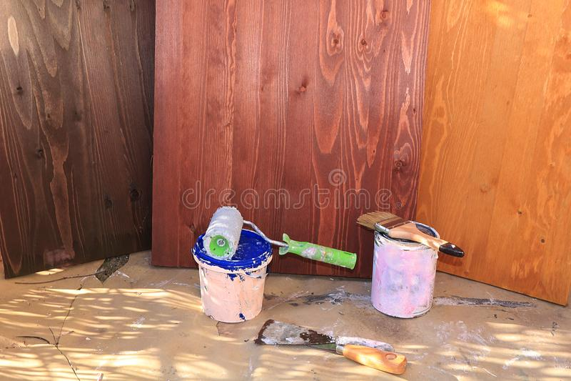 Painting wooden walls during the repair. Making wooden backgrounds for a photo with your own hands. Repair work in the new house, brushes, paints and paints stock photography