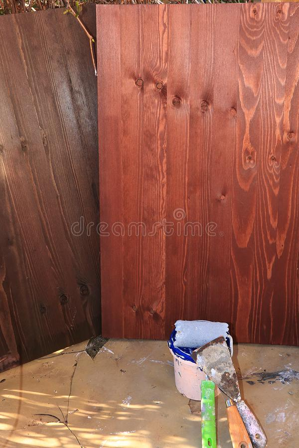 Painting wooden walls during the repair. Making wooden backgrounds for a photo with your own hands. Repair work in the new house, brushes, paints and paints stock photo