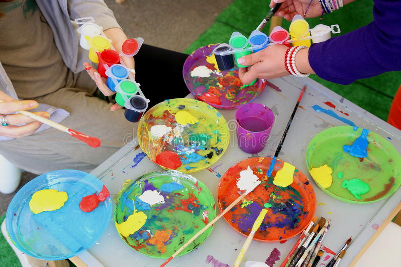 Painting workshop. Young women preparing different colors on the work table with paint brush stock photo