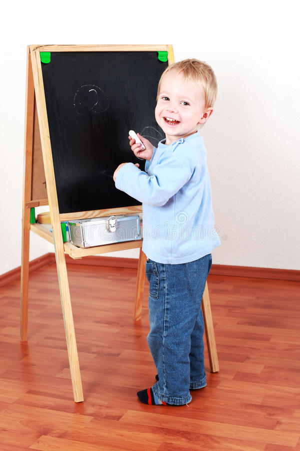 Painting and writing. Adorable boy playing with chalkboard stock image