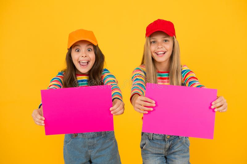 Paintings exhibition. Children gallery modern art. Modern kids with pictures. Charity market. Girls hold modern poster. Blank pink paper sheets. Best friends stock photo