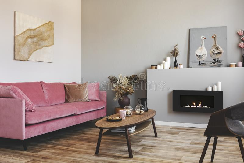 Paintings on the walls of grey living room interior with pink couch and bio fireplace.  royalty free stock images