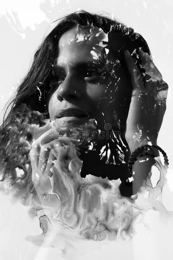 Paintography. Double Exposure portrait of a seductive ethnic woman with nose piercing and strong expression combined with hand dr stock photography