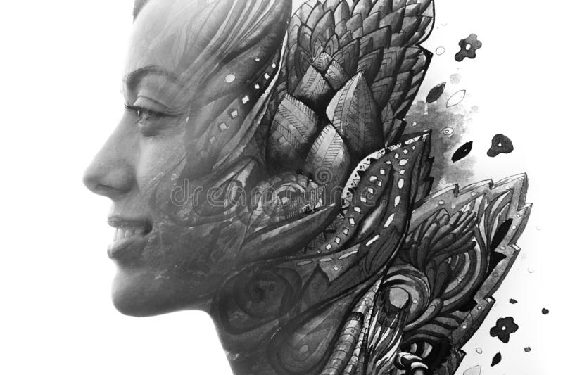 Paintography. Double exposure profile of a young natural beauty, with face and hair combined with hand drawn leaves dissolving royalty free stock photo
