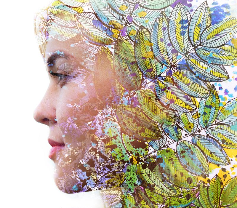 Paintography. Double exposure profile of a young natural beauty, with face and hair combined with colorful hand drawn leaves royalty free stock photography