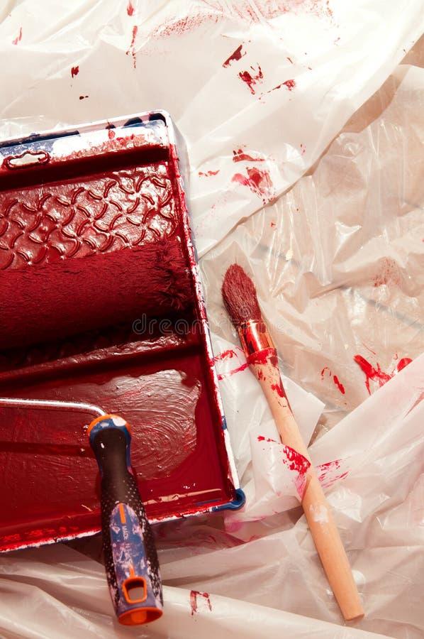 Paintroller e pincel cobertos na pintura vermelha foto de stock