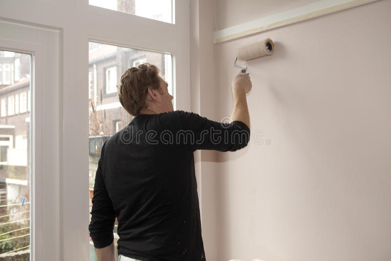 Paintroller on wall stock image