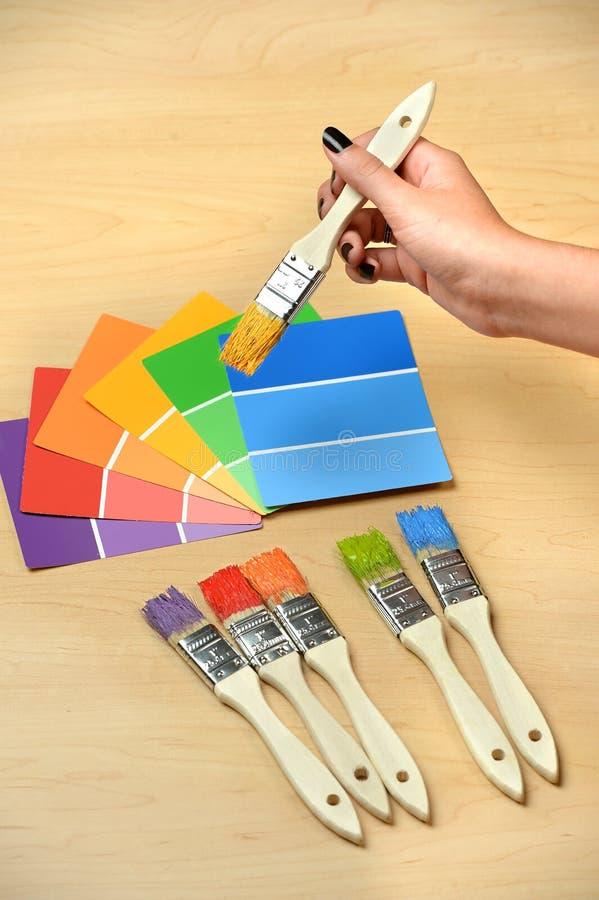 Paintrushes e campioni con la spazzola della tenuta della mano immagini stock