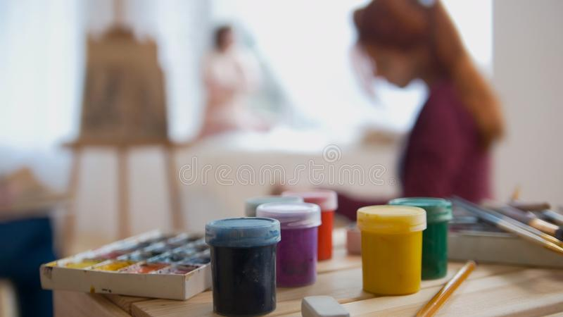 Paints and art supplies in front of artists performing artistic etude witn naked model royalty free stock images