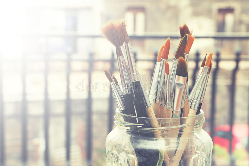 Paints and brushes. Photo of paint brushes in a jar stock image