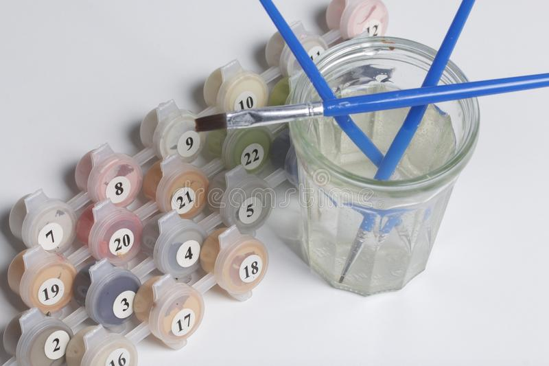 Paints for drawing by numbers. Several containers with paint are open. There are tassels, a sheet of paper nearby. Paints for drawing by numbers. Several royalty free stock photo