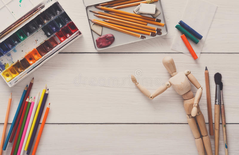 Paints and wooden painter man with brushes, object. Painting visual art background. Paints and wooden painter man with brushes on white desk, top view, flat lay royalty free stock image
