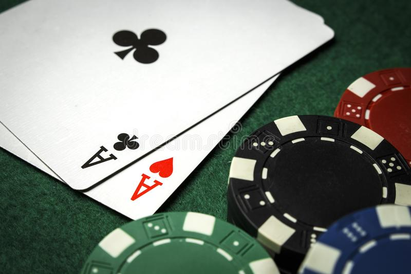 A pair of aces with a pile of poker chips stock image