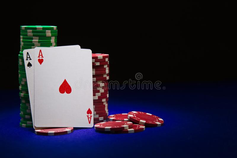 Pair of aces on stuck of chips. On blue table royalty free stock photography